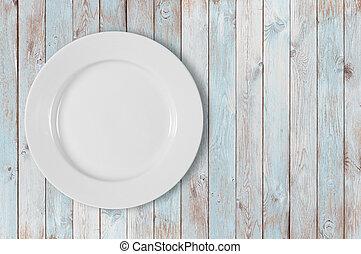 white empty dinner plate on left side of blue wooden table
