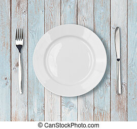 white empty dinner plate setting on blue wooden table