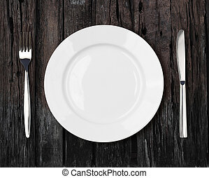 white empty dinner plate setting on old dark wooden table