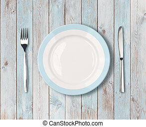 white empty dinner plate with blue border on wooden table