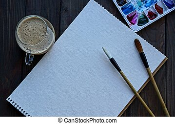 white empty notebook with brushes and a set of colors and a cup of coffee on a black table