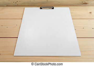 white empty plastic clipboard lay on the wood table.