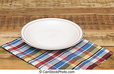 white empty plate on colorful napkin