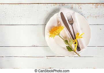 White empty plate, yellow chrysanthemum flowers, napkin,...
