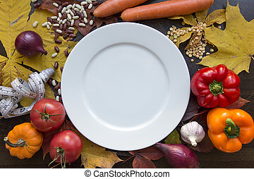 White emty plate with measuring tape and vegetables top view