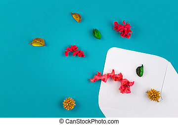 White envelop and colorful dried flowers, plants on blue background. Top view, flat lay