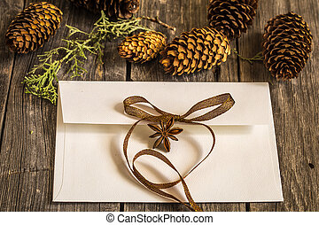 White envelope on wooden background with pine cones and Christmas gift