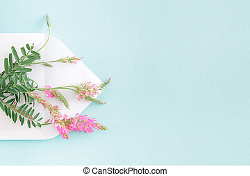 White envelope with pink flowers on blue background. mail for you