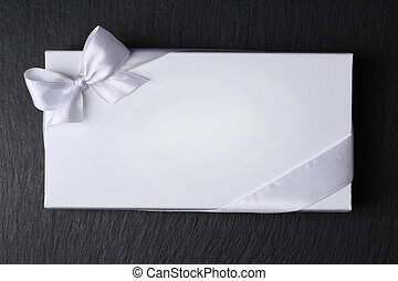 White envelope with ribbon on black background