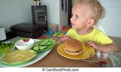 White european little kid eating tasty big burger with great appetite. Gimbal stabilizer movement motion shot.