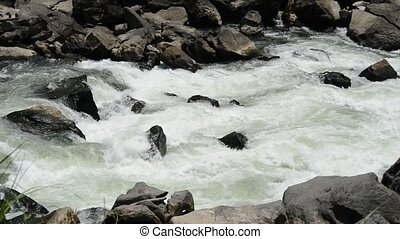 White fast river stream between a lot of rocks