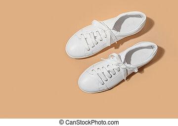 White female gumshoes on beige background. View from above. Copy space.