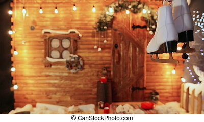 White female skates on the background of a wooden fairy house. Christmas and New Year theme.