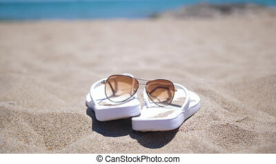 White female slippers and sunglasses on the beach near the splashing waves