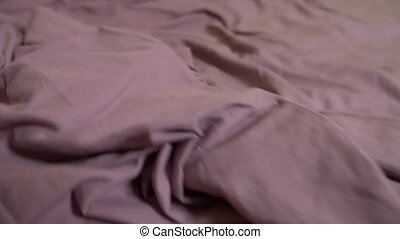 white female vibrator on crumpled lilac sheets. - white...