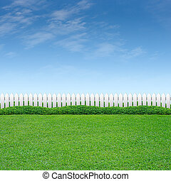 White fence and green grass on blue sky