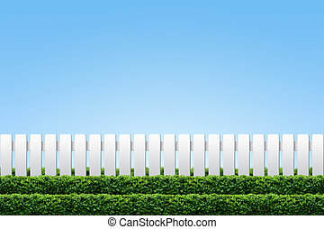 White fence and hedge on clear blue sky