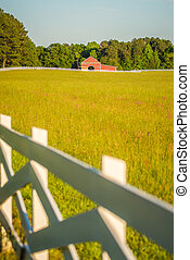 white fence leading up to a big red barn