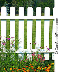 White fence on green grass and flowers. - White fence on...