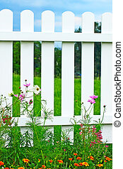 White fence on green grass and flowers.