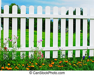 White fence on green grass with flowers.