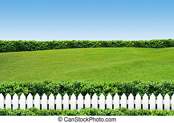 White fence with grass on clear blue sky