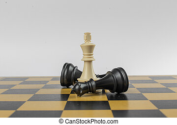 White figure in the center and blacks around on a chessboard on isolated white background