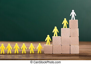 White Figure Leading Human Figures On Top Of Wooden Blocks