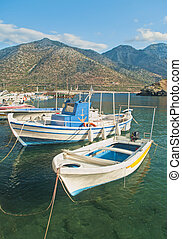 white fishing boats in small mountainous harbour - small...