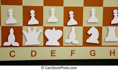 White flat chessmen at starting position on board, shown in...