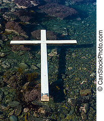 White cross floating on clear water.