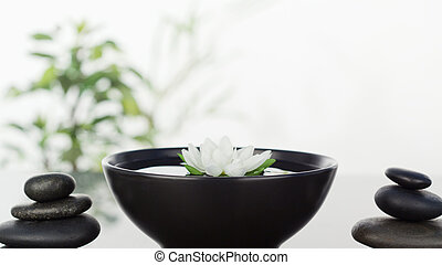 White flower floating in bowl in th middle and two stacks of...