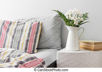 White flowers and books on a side table near a bed. Fresh design.