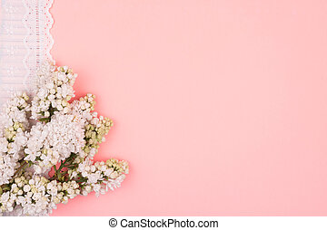 White flowers and lace on a pink background.
