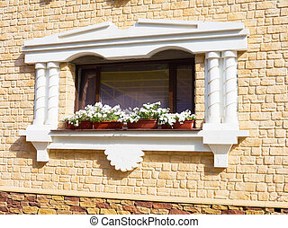 White flowers hangs on the window of a home in an ancient building ,