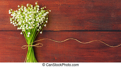 white flowers lilies of the valley on brown wooden boards. Copy space. Free space for text