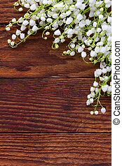 white flowers lilies of the valley scattered on the old wooden brown background. with space for text
