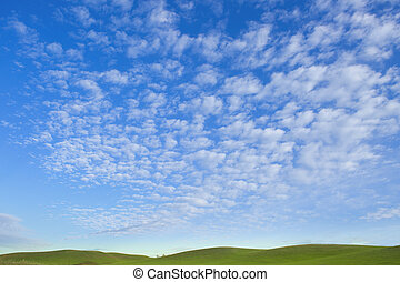 White fluffy clouds in the blue sky and green hills