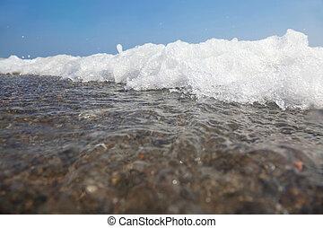 white foam of sea waves, splashes ashore. blue sky. hot summer.