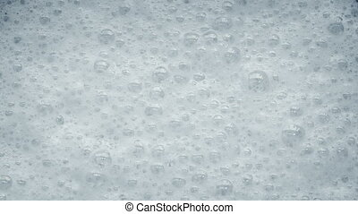 White Foam With Bubbles Popping - Closeup of white foam with...