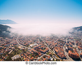 White fog is coming from the sea to the city of Budva in Montenegro.