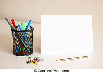 White folded sheet of paper on the table. Nearby are pens and pencils.