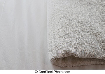White folded towels placed on the bed.