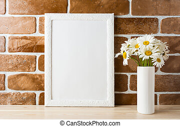 White frame mockup with daisy bouquet near exposed brick...