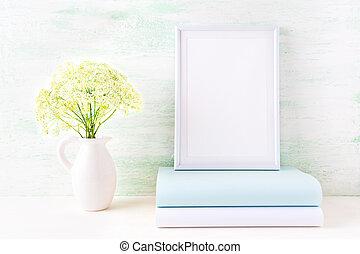 White frame mockup with pale mint book. Empty frame mock up for presentation artwork.