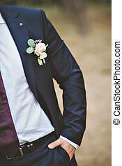 White freesia wedding boutonniere on suit of groom