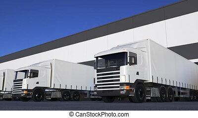 White freight semi trucks loading or unloading. Road cargo...