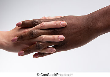 African-American woman shaking hand of friend with white skin