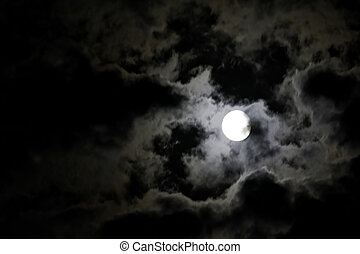 White full moon and eerie white clouds against a black night sky