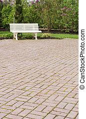 White garden bench on paved walk